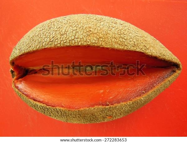 Mamey sapote fruit on orange cutting board