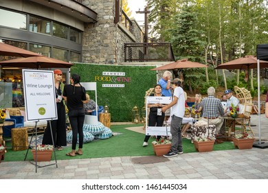 Mammoth Lakes, California - July 12, 2019: People gather at a booth at the Mammoth Food & Wine Experience summer festival