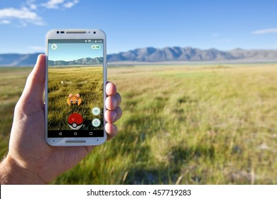 """MAMMOTH LAKES, CALIFORNIA - JULY 21, 2016: The hit augmented reality smartphone app """"Pokemon GO"""" shows a Pokemon encounter overlain on a grassy field in the real world."""