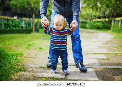 Man with 1 year old baby girl in park. Father helping his daughter make first steps. Toddler learning how to walk. Family activities with kids