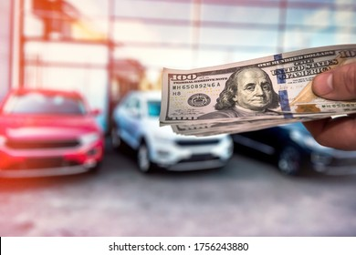 Man with 100 dollar banknotes money near car. Buy or rent a new auto. Finance concept