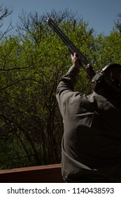 Man with a 12-gauge shotgun takes aim at a clay pigeon at a skeet shooting practice range. Color, vertical image, with space for copy.