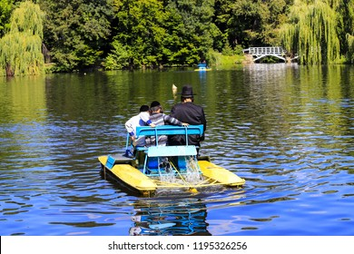 A man with 2 children, Hasidic Jews, ride a catamaran on a lake in the autumn Sofia park in Uman, Ukraine, during the Jewish New Year, Rosh Hashanah