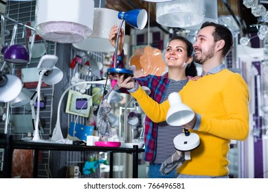 Man 29-35 and woman 18-20 years old in shop of home appliances are choosing table lamp for home.