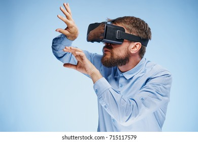 man in 3D glasses plays virtual reality games on a blue background