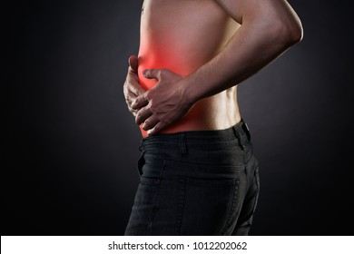 Man with abdominal pain, stomach ache on black background, with red dot
