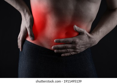 Man with abdominal pain, stomach ache on black background, painful area highlighted in red