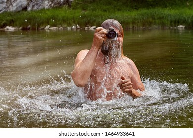 Man about 50 years old is taking photos with waterproof camera during swimming in the river while eco-tourism.