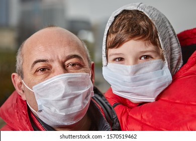 Man about 50 years old and little boy are posing in medical masks on their faces as a protection from flu. Father and son with respiratory mask on face to protect from air pollution.