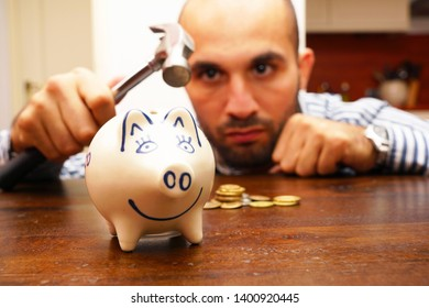 Man is about to break a piggy bank with a hammer.