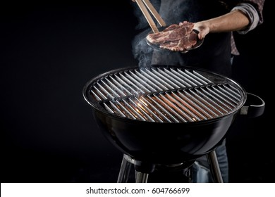 Man about to place raw meat on a hot BBQ fire with glowing coals taking a portion of steak in tongs from a plate in his hand
