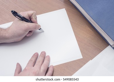 A man is about to write something on the piece of paper