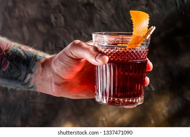 Man with an abstract tattoo on his hand is holding a faceted glass with the Negroni alcoholic drink on a dark textured background. Close-up. Space