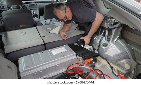 A man accessing the hybrid battery fan in 2011 Toyota Prius in order to clean it. Photo taken in Vista, CA / USA on June 4, 2020.