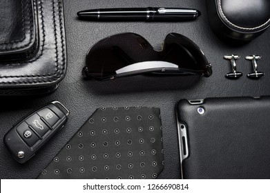 Man accessories in business style, clothes, gadgets, jewelry, sunglasses and other luxury businessman attributes on leather black background, fashion industry, selective focus