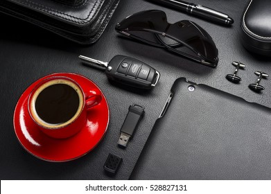 Man accessories in business style with cup of coffee, gadgets, car key, cufflinks, sunglasses, briefcase and other luxury businessman attributes on leather black background, fashion industry