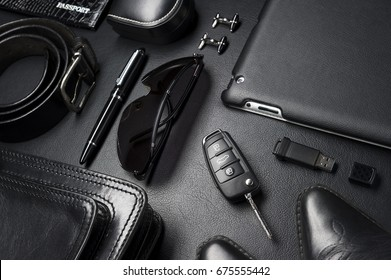 Man accessories in business style, gadgets, clothes, shoes, jewelry, and other luxury businessman objects on leather black background, fashion industry, selective focus