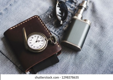 Man accessories, watch, wallet, e cigarette and glasses on blue jeans