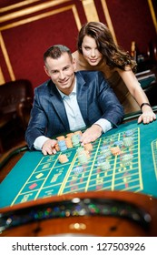 Man accompanied by woman placing bets at the roulette table