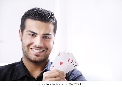 man with ace poker; four aces in hands; smiling and looking in camera.