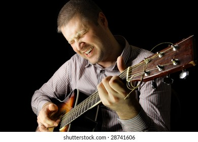Man with acoustic guitar over black background