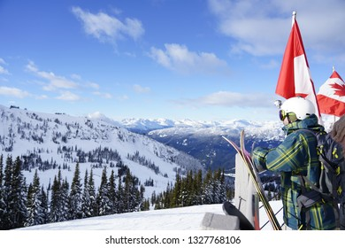 Man with action camera attached on his helmet holding snowboarding gears looking outward at snowy slopes underground clear blue sky