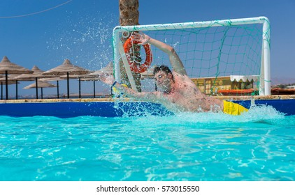 Man in action skips the goal in pool playing water polo at the hotel on a sunny summer day
