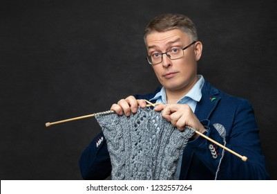 A man is active with his hobby knitting. a man dressed in a suit and shirt knits a jacket with wooden spokes on a dark background of the Studio and looks at the camera