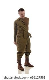 Man actor dresses or removes the military uniform of an American tankman of the period of World War II posing against a white background