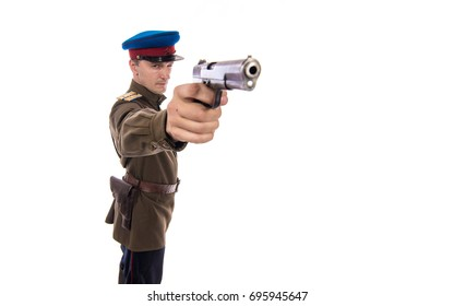 Man actor in the form of an officer captain People's Commissariat of Internal Affairs of Russia from the period 1943-1945 aims and is preparing to shoot a pistol on a white background