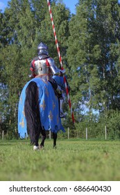 Man actor in knightly armor with a spear in his hands rides a horse through the woods