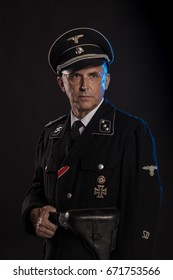 Man actor in military uniform of the Second World War, posing on a black background in a blue scenic light