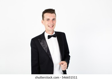 Man actor performing on the stage. Smiling man on white background looks at the camera. Copy space. Young man in classic black suit on white background