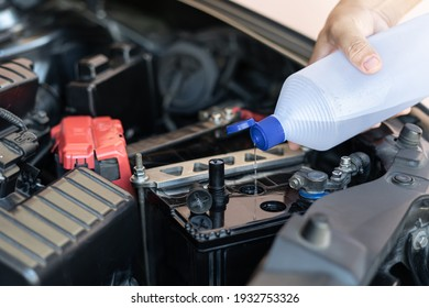 A man add water to distilled the car battery maintenance and inspections for extended service life of car