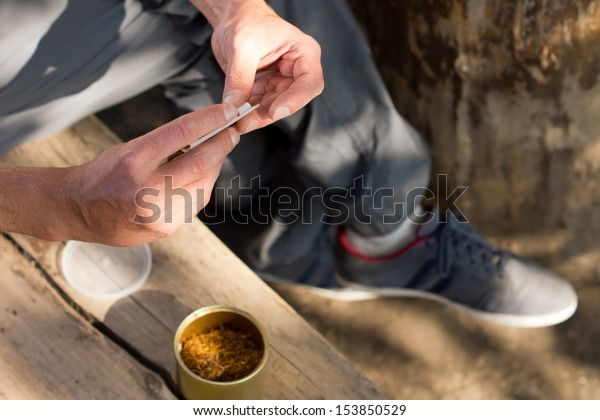 Man addicted to marijuana or cannabis rolling himself a joint sitting outdoors in the shade, close up view of the hands