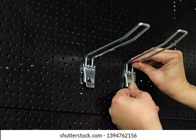 Man adding hooks to pegboard for the product presentation at the store.