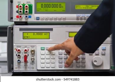 a man adjust a parameter of calibrator meter to make a calibration of electronic meter