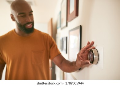 Man Adjusting Digital Central Heating Thermostat At Home