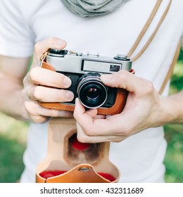 Man adjusts a retro film camera before snapshot against the backdrop of green forest, close shot of hands and camera