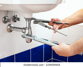 man adjusts two old pipe-wrenches to install a sink siphon in bathroom