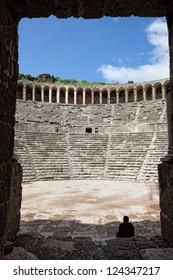Man admiring the ancient theater of Aspendos through a doorway