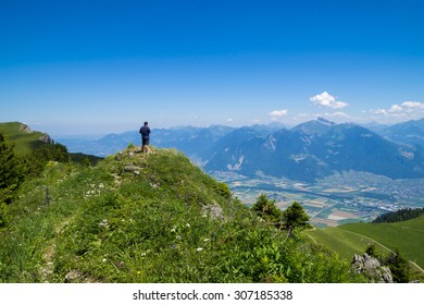 Man admiring the landscape. Hiking in the Alps Mountains, in touristic region Portes du Soleil, France and Switzerland together.