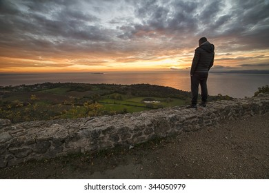 A man admiring the sunrise over the lake from the mountain