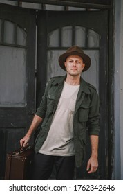 Man in adventure outfit walking around village wearing a fedora, vintage feeling. The individual is wearing a green jacket with satchel and has a vintage traveller look. Person is caucasian.