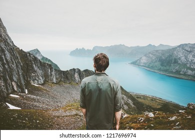 Man adventurer admiring fjord and mountains view Travel lifestyle adventure concept vacations outdoor in Norway solitude calm emotions