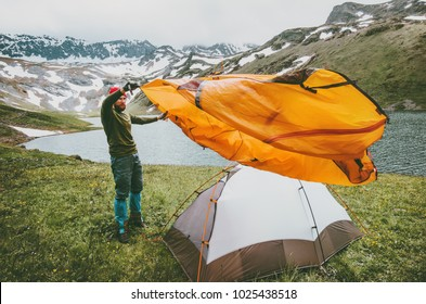 Man adventurer pitching tent camping gear outdoor Travel survival lifestyle concept summer trip vacations in mountains