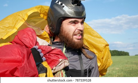 Man After Paragliding. Glider With Parachute After Flying An Extreme Sports Event On A Paraglider. Person Have Fly On Paraglider On Background Of Green Grass On Sunny Day