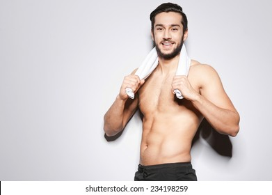Man after workout. Handsome young man with towel on shoulders looking at camera and smiling while standing against grey background