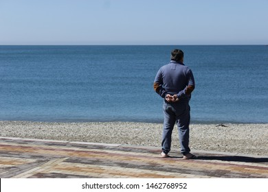 The man is against the background the blue sea. A lonely male stands on the shore of the Black Sea.