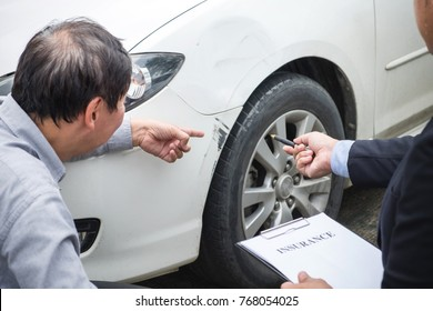 Man agent Filling Insurance Form Near Damaged and examining Car, Traffic Accident and insurance concept.